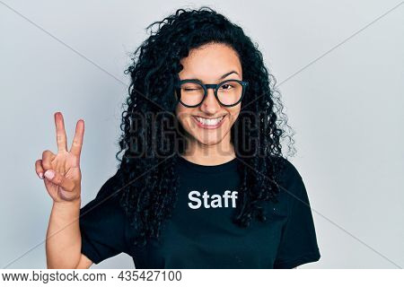 Young hispanic woman with curly hair wearing staff t shirt smiling with happy face winking at the camera doing victory sign with fingers. number two.