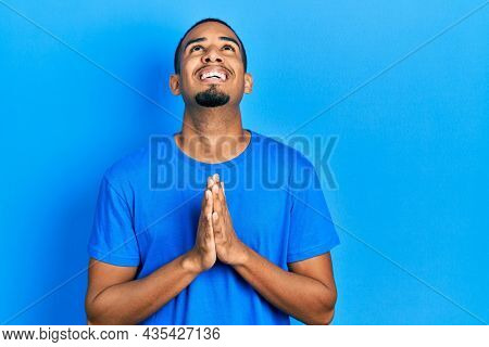 Young african american man wearing casual blue t shirt begging and praying with hands together with hope expression on face very emotional and worried. begging.