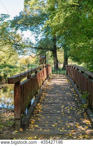 Wooden Bridge Ahead Across A Small River In The Woods. Garden Architecture
