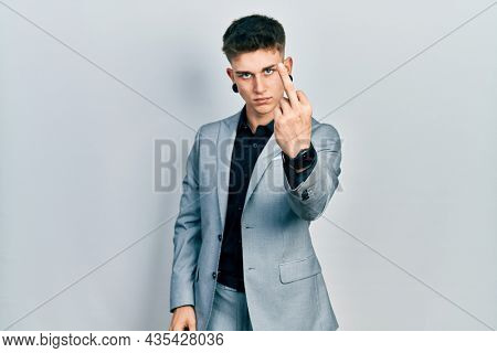 Young caucasian boy with ears dilation wearing business jacket showing middle finger, impolite and rude fuck off expression