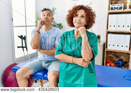 Physiotherapy woman working at pain recovery clinic with patient serious face thinking about question with hand on chin, thoughtful about confusing idea