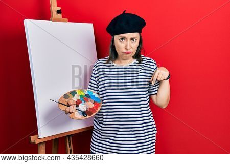 Middle age hispanic woman standing drawing with palette by painter easel stand pointing down looking sad and upset, indicating direction with fingers, unhappy and depressed.