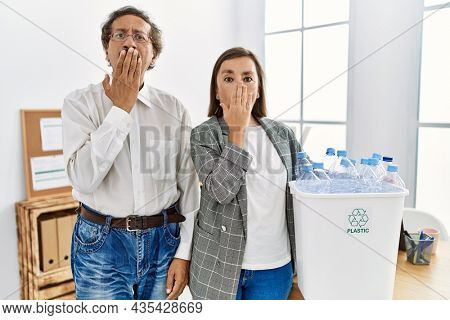 Middle age interracial couple holding recycling bin with plastic bottles at the office covering mouth with hand, shocked and afraid for mistake. surprised expression