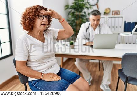 Senior woman sitting at doctor appointment very happy and smiling looking far away with hand over head. searching concept.