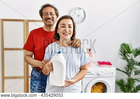 Middle age interracial couple doing laundry holding detergent bottle looking positive and happy standing and smiling with a confident smile showing teeth