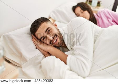 Young hispanic couple sleeping on bed at home.