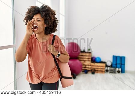 African american woman with afro hair holding yoga mat at pilates room shouting and screaming loud to side with hand on mouth. communication concept.