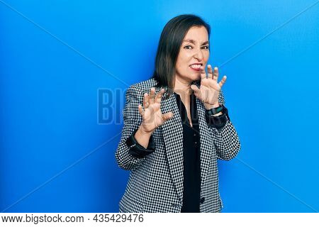 Middle age hispanic woman wearing business clothes disgusted expression, displeased and fearful doing disgust face because aversion reaction. with hands raised