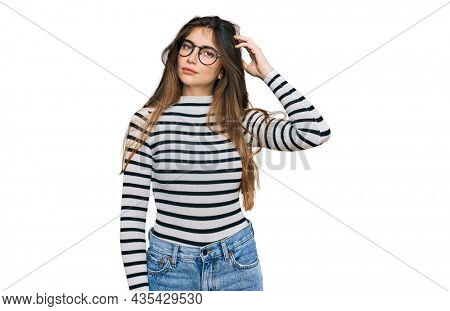 Young beautiful teen girl wearing casual clothes and glasses confuse and wonder about question. uncertain with doubt, thinking with hand on head. pensive concept.