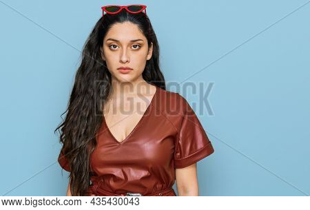 Brunette young woman wearing dress and sunglasses skeptic and nervous, frowning upset because of problem. negative person.