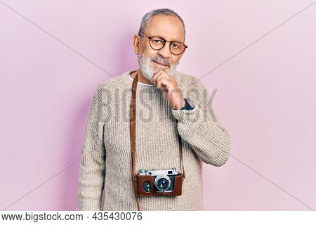 Handsome senior man with beard holding vintage camera smiling looking confident at the camera with crossed arms and hand on chin. thinking positive.