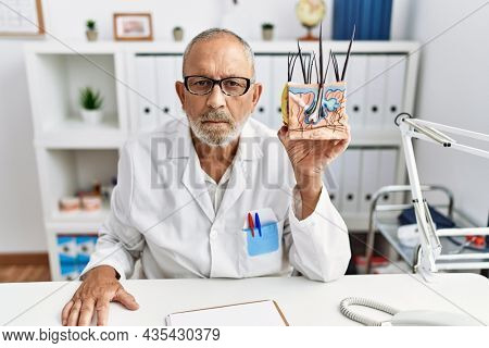Mature doctor man holding model of human anatomical skin and hair thinking attitude and sober expression looking self confident
