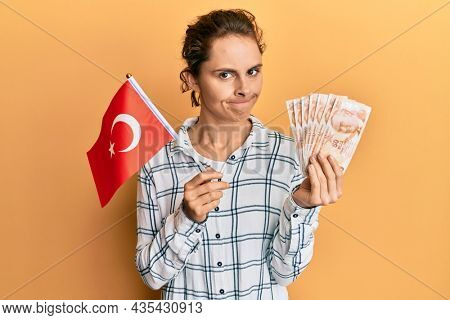 Young brunette woman holding turkey flag and liras banknotes skeptic and nervous, frowning upset because of problem. negative person.