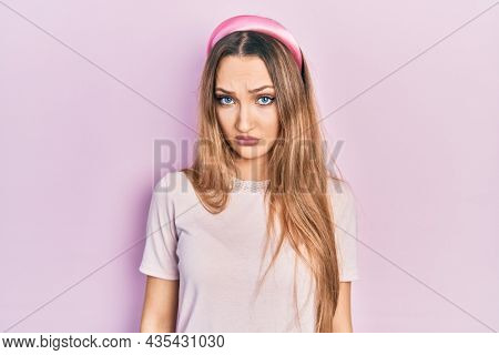 Young blonde girl wearing casual clothes skeptic and nervous, frowning upset because of problem. negative person.