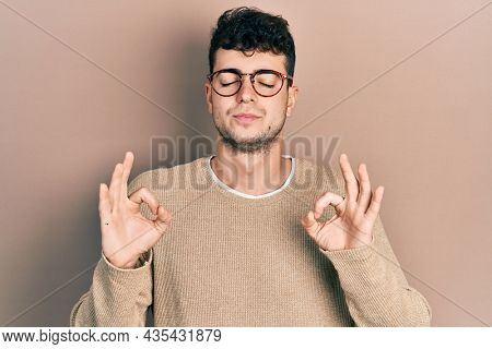 Young hispanic man wearing casual clothes and glasses relaxed and smiling with eyes closed doing meditation gesture with fingers. yoga concept.