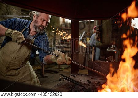 Professional Smith In Gloves Burning The Flame In The Furnace With Adding Coals