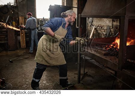 Craftsman Adding Coal In Furnace In The Blacksmith Shop