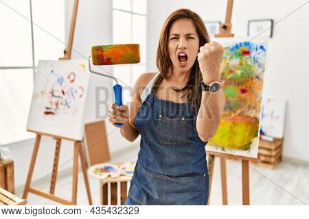 Young latin artist woman holding paint roller standing at art studio annoyed and frustrated shouting with anger, yelling crazy with anger and hand raised