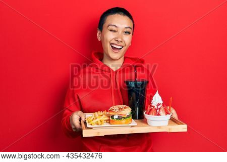 Beautiful hispanic woman with short hair eating a tasty classic burger with fries and soda winking looking at the camera with sexy expression, cheerful and happy face.