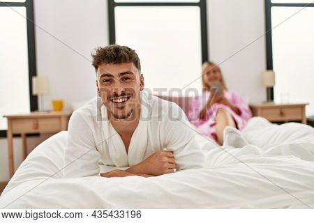 Young caucasian couple smiling happy lying on the bed at home.