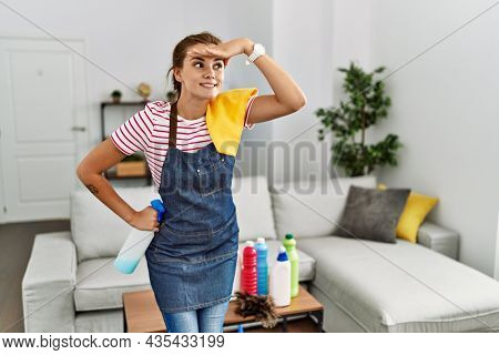 Young brunette woman wearing apron holding cleaning products at home very happy and smiling looking far away with hand over head. searching concept.