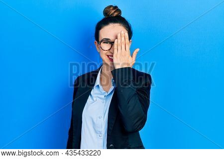 Young hispanic girl wearing business clothes and glasses covering one eye with hand, confident smile on face and surprise emotion.