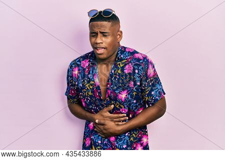 Young black man wearing hawaiian shirt and sunglasses with hand on stomach because nausea, painful disease feeling unwell. ache concept.