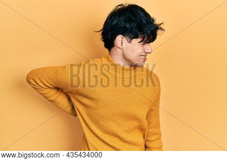 Handsome hipster young man wearing casual yellow sweater suffering of backache, touching back with hand, muscular pain