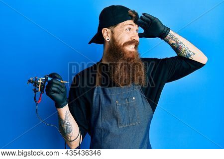 Redhead man with long beard tattoo artist wearing professional uniform and gloves very happy and smiling looking far away with hand over head. searching concept.
