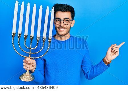 Young hispanic man holding menorah hanukkah jewish candle smiling happy pointing with hand and finger to the side