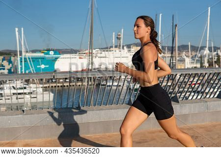 Focused Sportswoman In Sportswear Running On Embankment During Cardio Training In Cloudless Morning