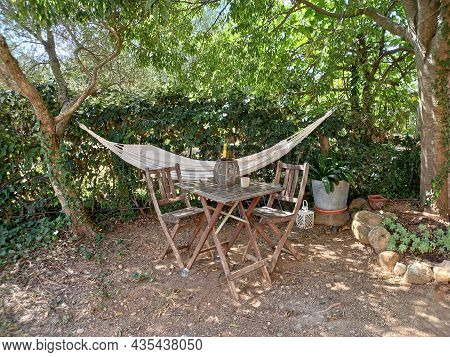 Hammock, Table And Wooden Chairs In Rustic Garden. Patio In Nature. Concept Of Rest And Relaxed Atmo