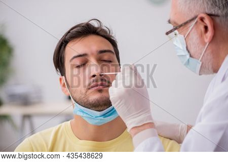 Young male patient visiting old male doctor otorhinolaryngologis