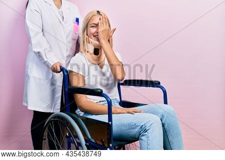 Beautiful blonde woman sitting on wheelchair with collar neck covering one eye with hand, confident smile on face and surprise emotion.