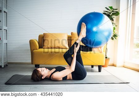 Asian Attractive Woman Wearing Black Gym Clothes Is Exercising, Toning Leg Muscles With A Blue Exerc