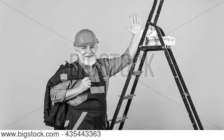 Tools For Repair. Senior Man Painter Use Roller On Ladder. Painting The Wall In Yellow. Professional