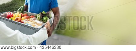 African Man Delivering Grocery Crate To Woman