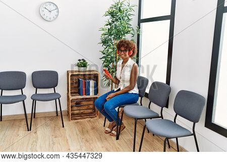 Young african american woman listening to music sitting on chair at waiting room