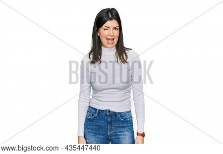 Beautiful brunette woman wearing casual clothes winking looking at the camera with sexy expression, cheerful and happy face.