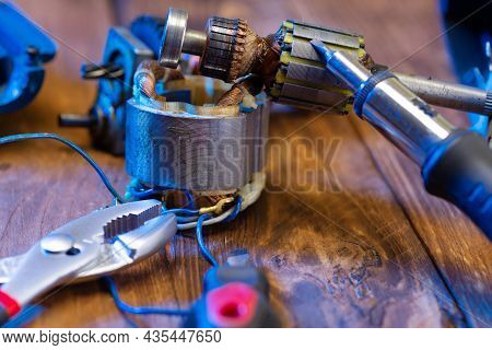 Power Tool Repair. Details Of An Electrical Appliance And Tools For Repair On A Wooden Table In A Re