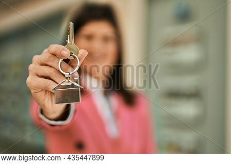 Middle age business woman working as real estate agent. Sales woman smiling happy showing house keys