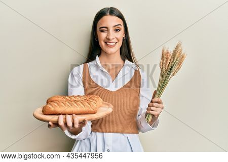 Beautiful brunette young woman holding homemade bread and spike wheat winking looking at the camera with sexy expression, cheerful and happy face.