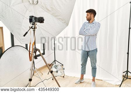 Arab young man posing as model at photography studio looking to the side with arms crossed convinced and confident