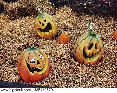Halloween Pumpkins Shrouded In Horror With Horror Atmosphere, With Eyes And Mouth Cut Into The Orang