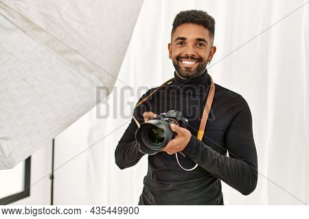 Handsome hispanic man working as professional photographer at photography studio. Standing holding camera smiling confident.