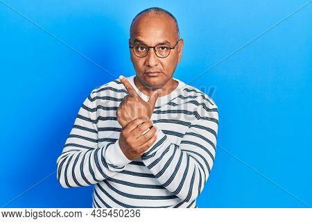 Middle age latin man wearing casual clothes and glasses holding symbolic gun with hand gesture, playing killing shooting weapons, angry face