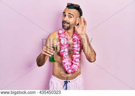 Young hispanic man wearing swimsuit and hawaiian lei drinking tropical cocktail smiling with hand over ear listening an hearing to rumor or gossip. deafness concept.