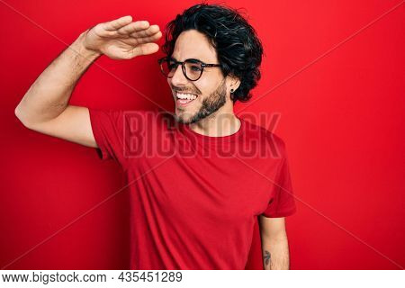 Handsome hispanic man wearing casual t shirt and glasses very happy and smiling looking far away with hand over head. searching concept.