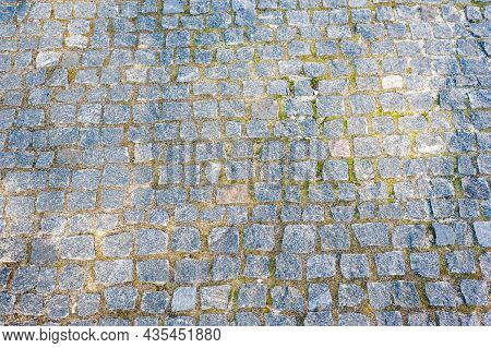 Paving Stones. Paved Road With Overgrown Grass. Cobblestone Surface. Selective Focus.