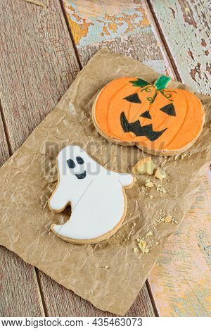Halloween-themed Buttery Cookies Next To Crumbs On Brown Paper.